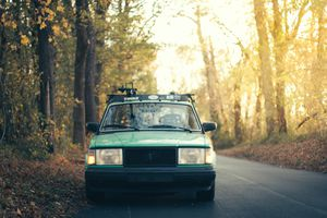 1980s Volvo sedan on a road in the forest