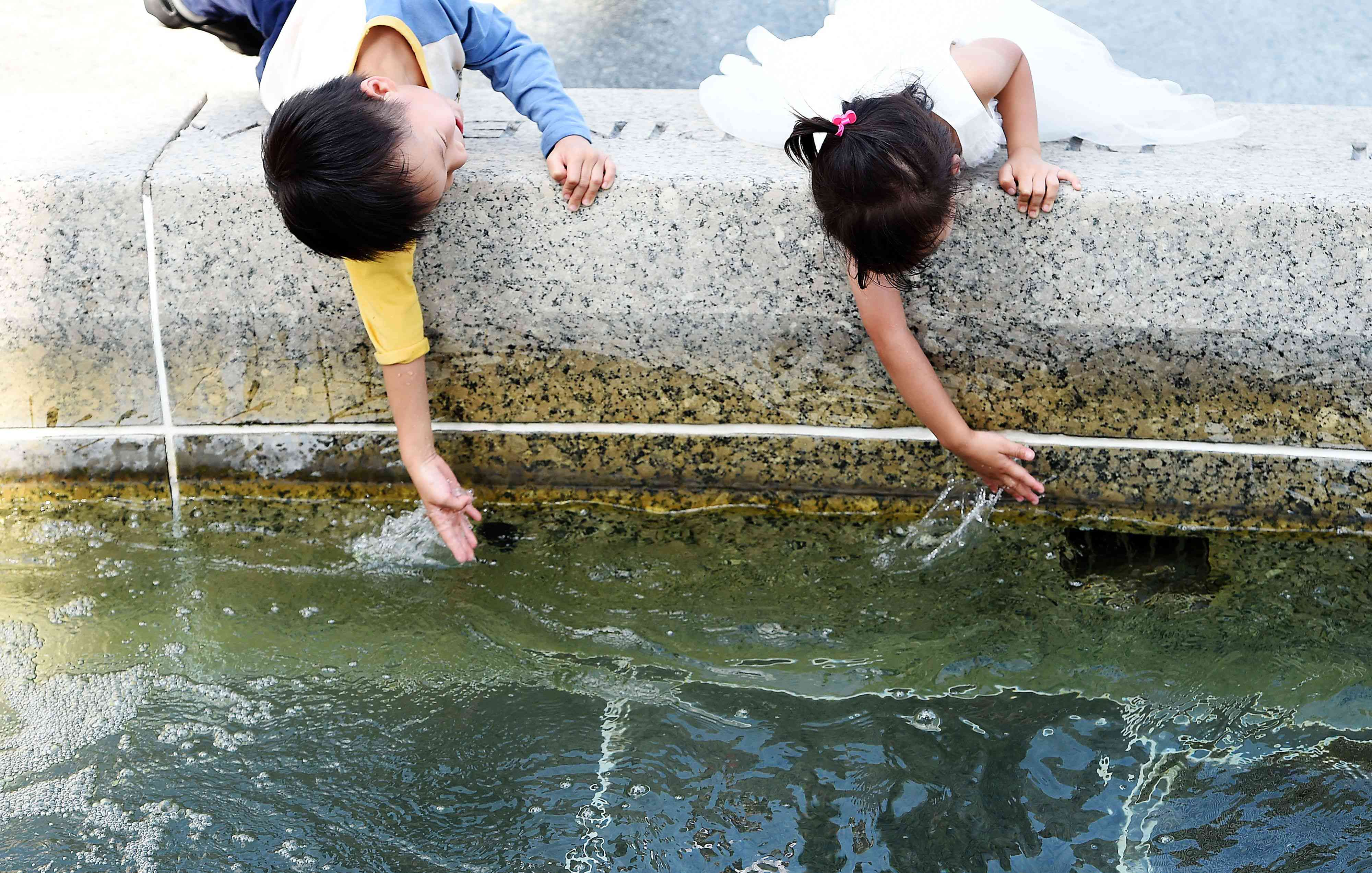 Kids playing in a water fountain.