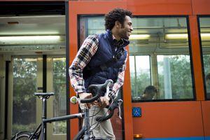 A Black man pushing a bike off of a city bus.