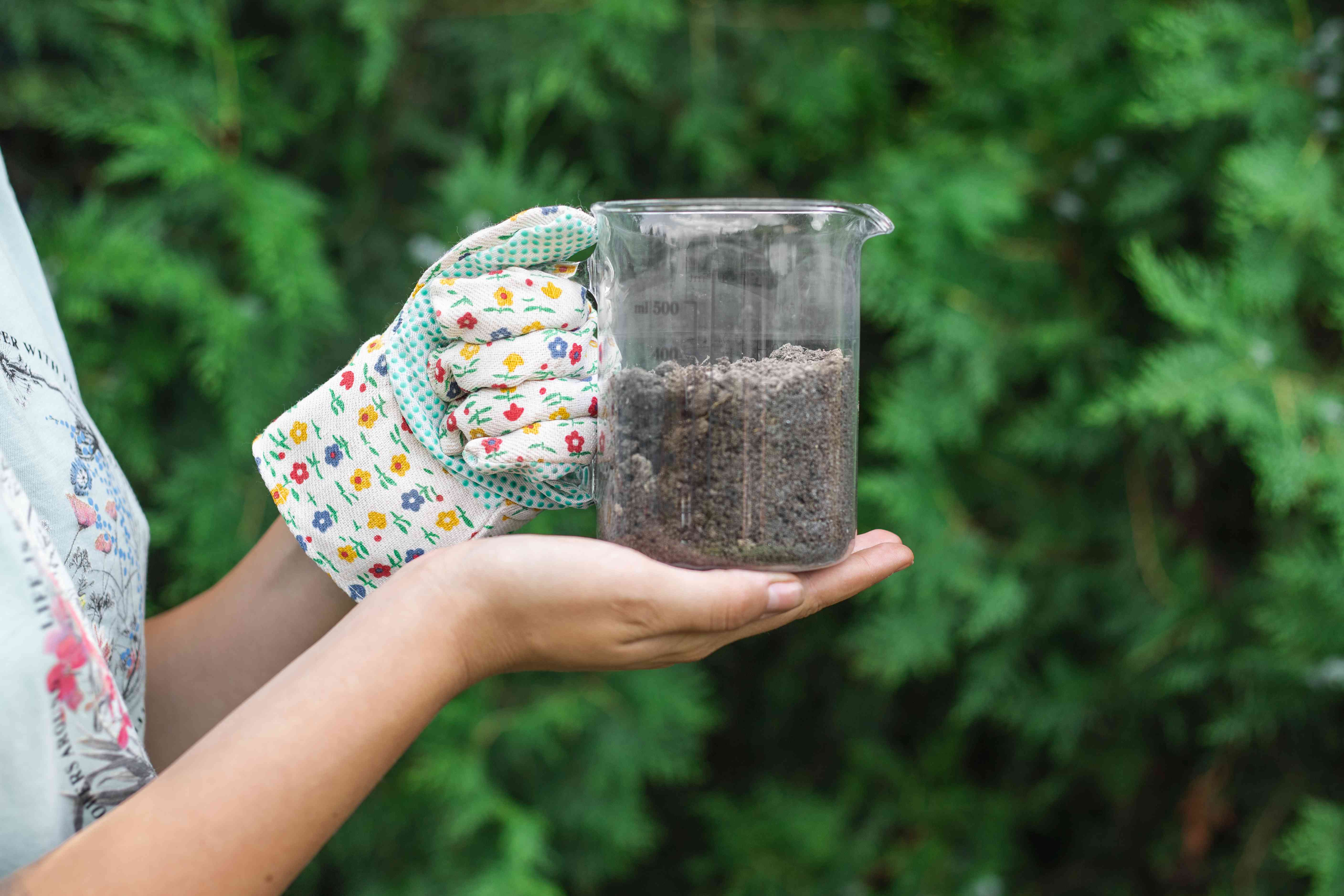 person wearing one gardening glove displays garden soil in glass cup reading for ph testing