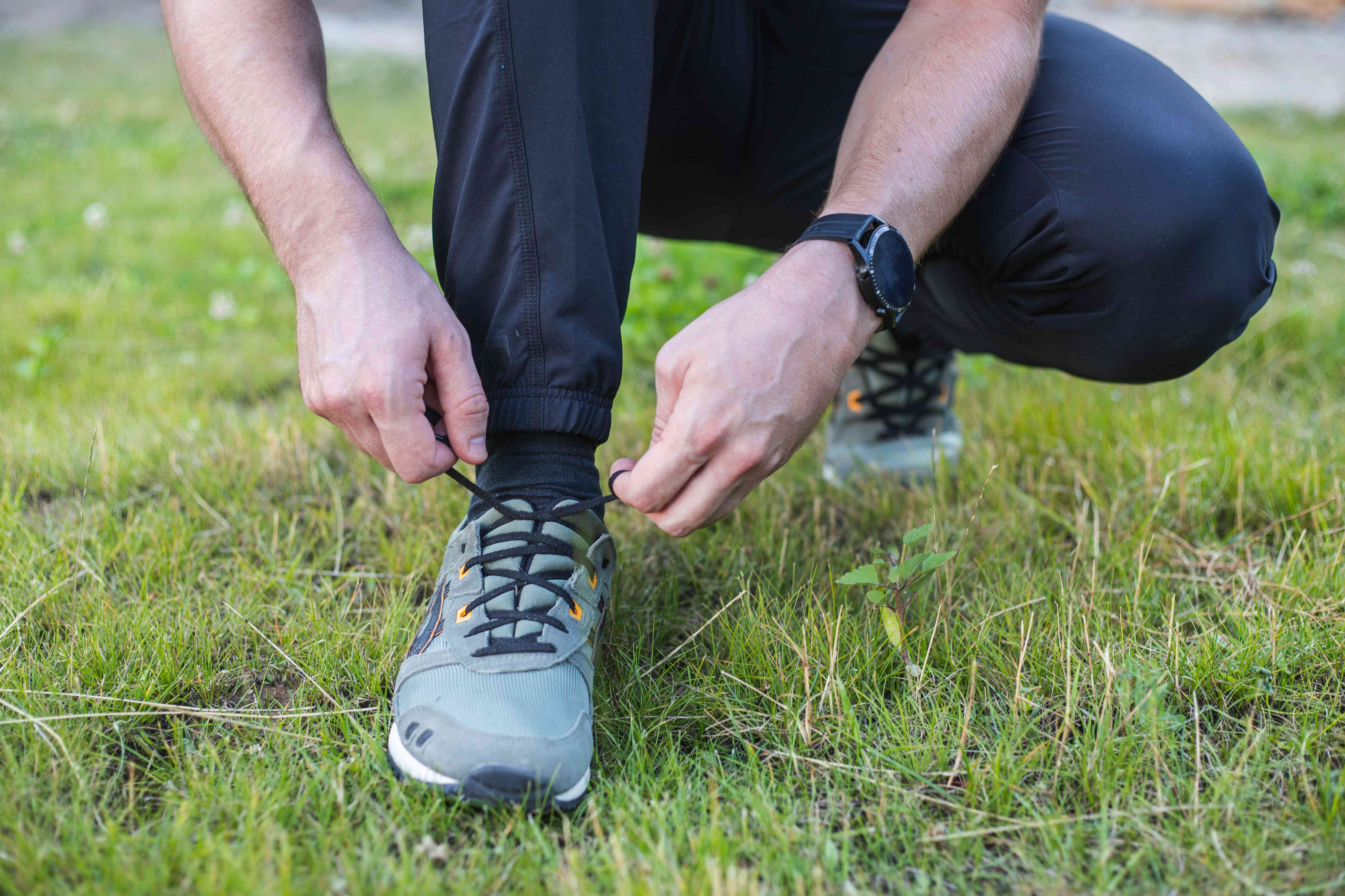 man in workout clothes crouches down to tighten laces on walking running shoes