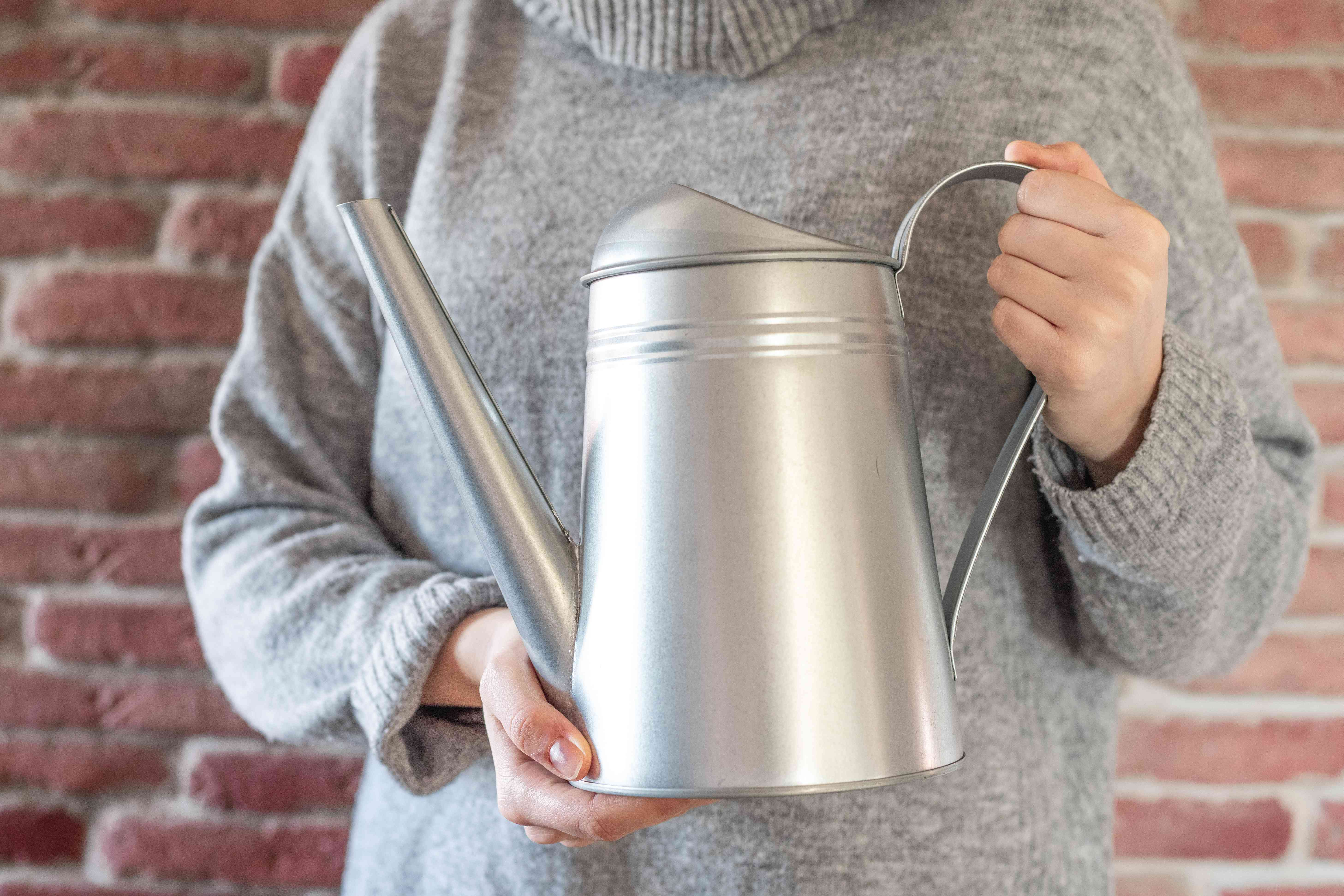 person in gray sweater faces camera cradling metal watering can