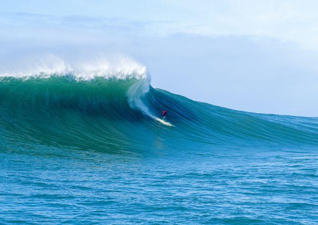 A surfer braves the waves along Moss Beach