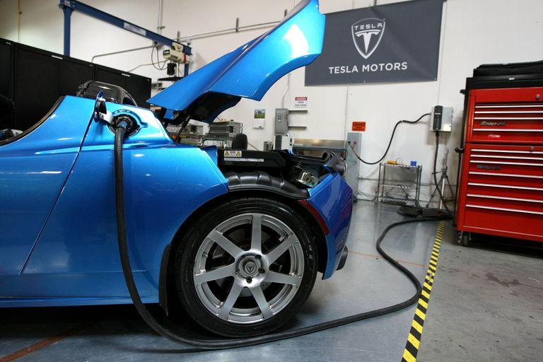 A blue Tesla Roadster car recharging.