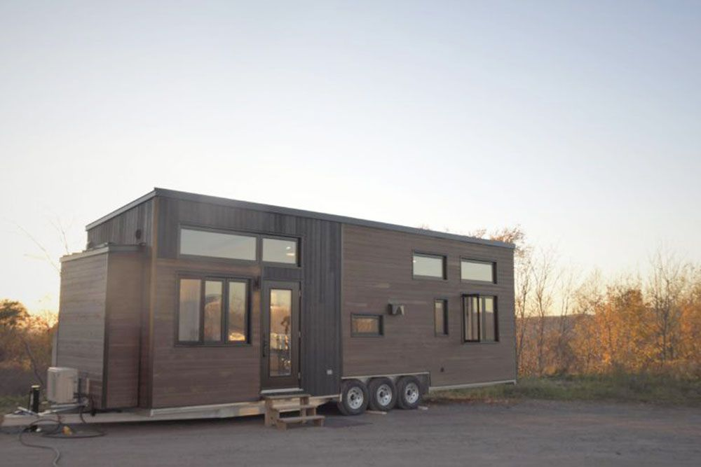 Exterior of dark-paneled tiny home on a trailer with wheels