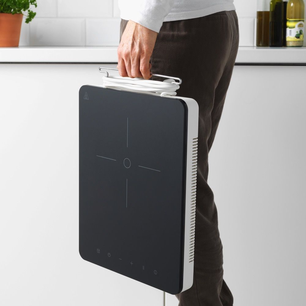 A person's hand carrying a portable stovetop unit