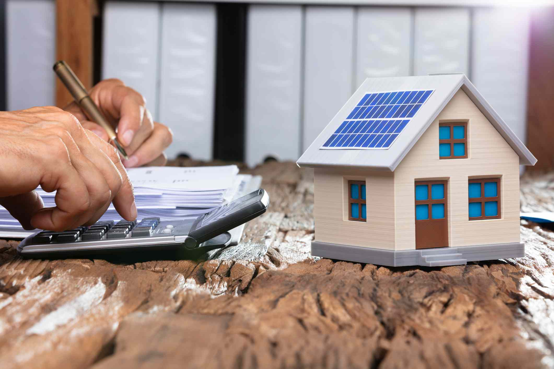 Person using a calculator next to a model solar home.
