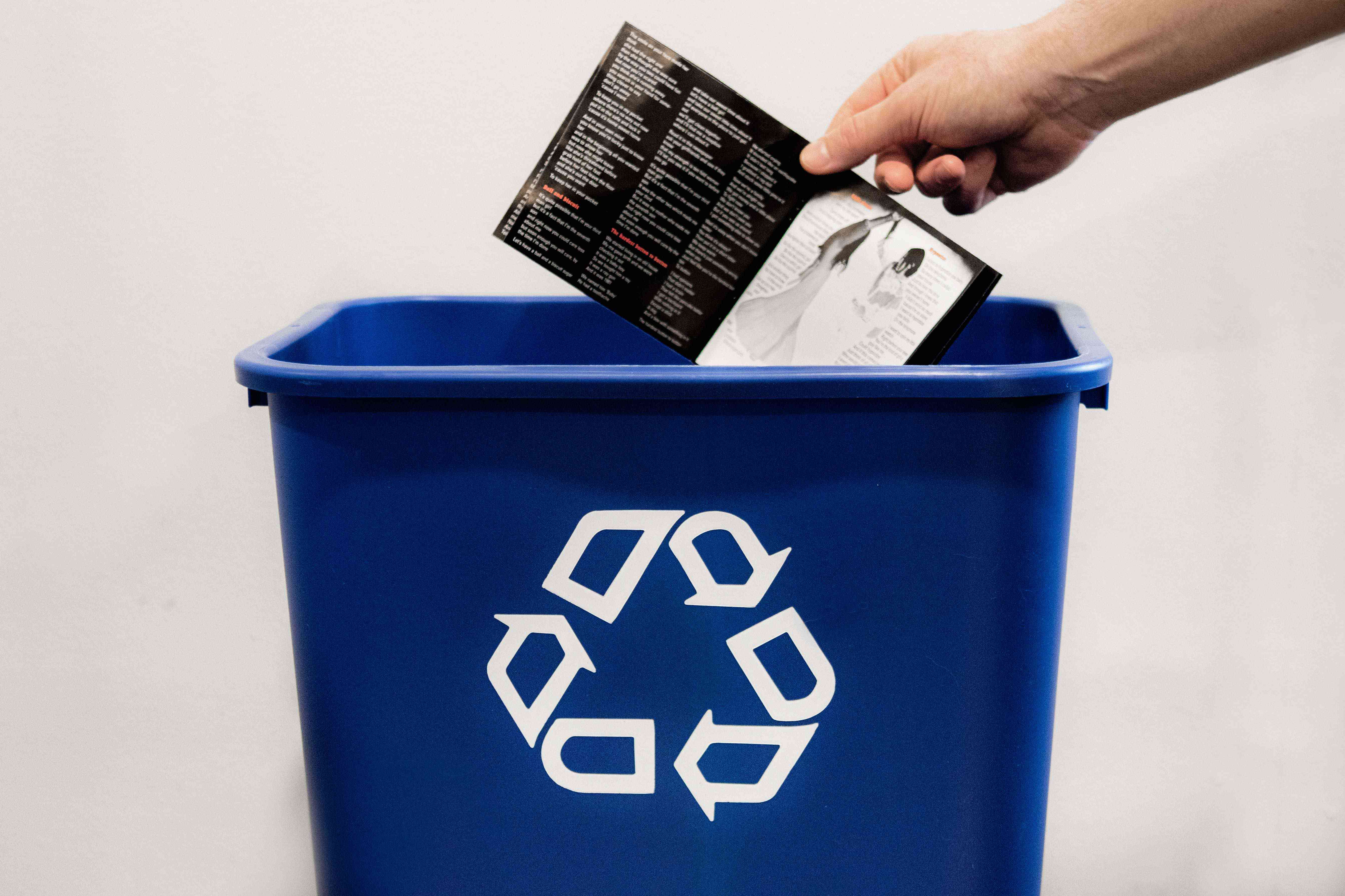 hand drops off paper liner off CD case into blue recycling bin