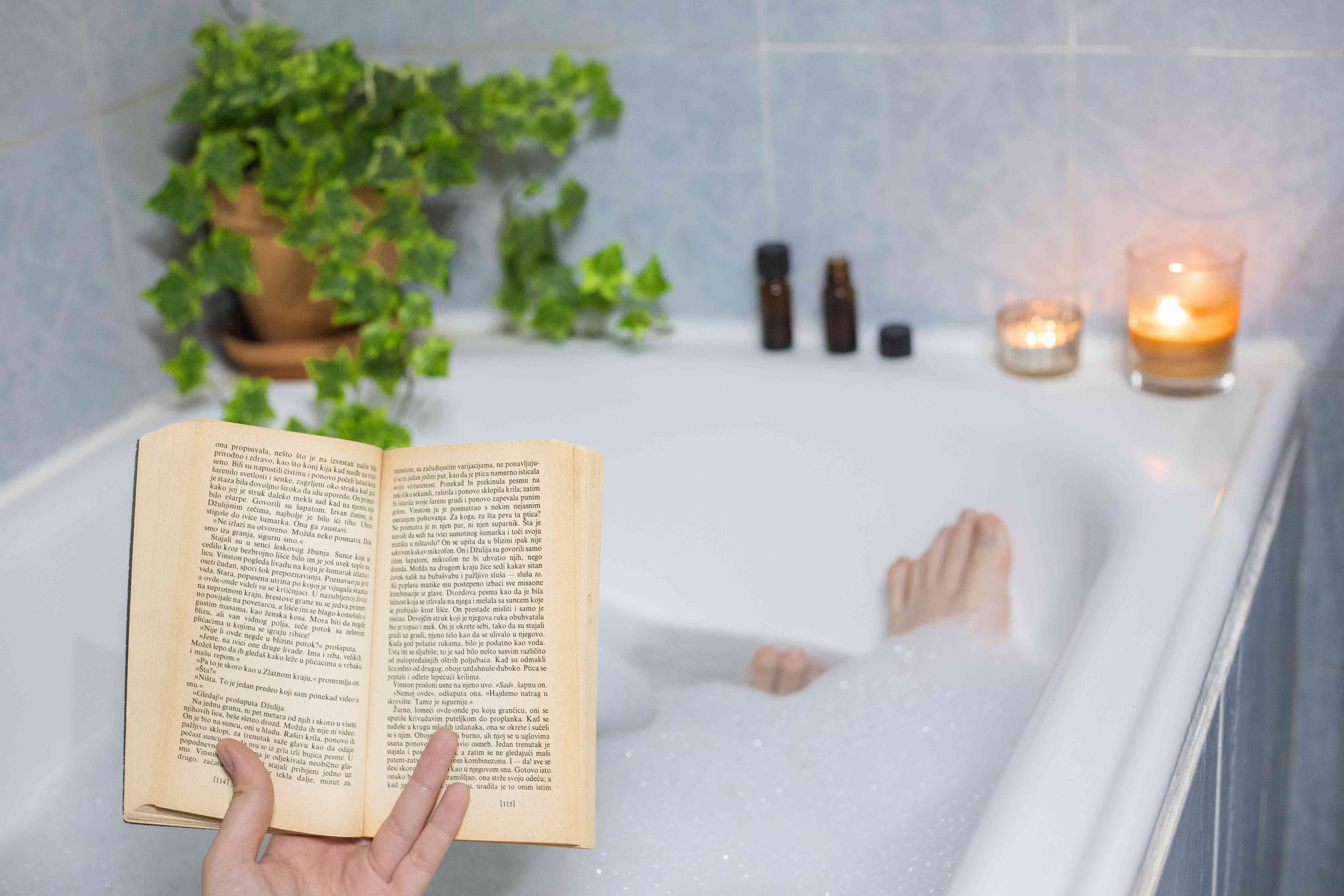 person relaxes in bubble bath while reading a book with candles lit and ivy plant