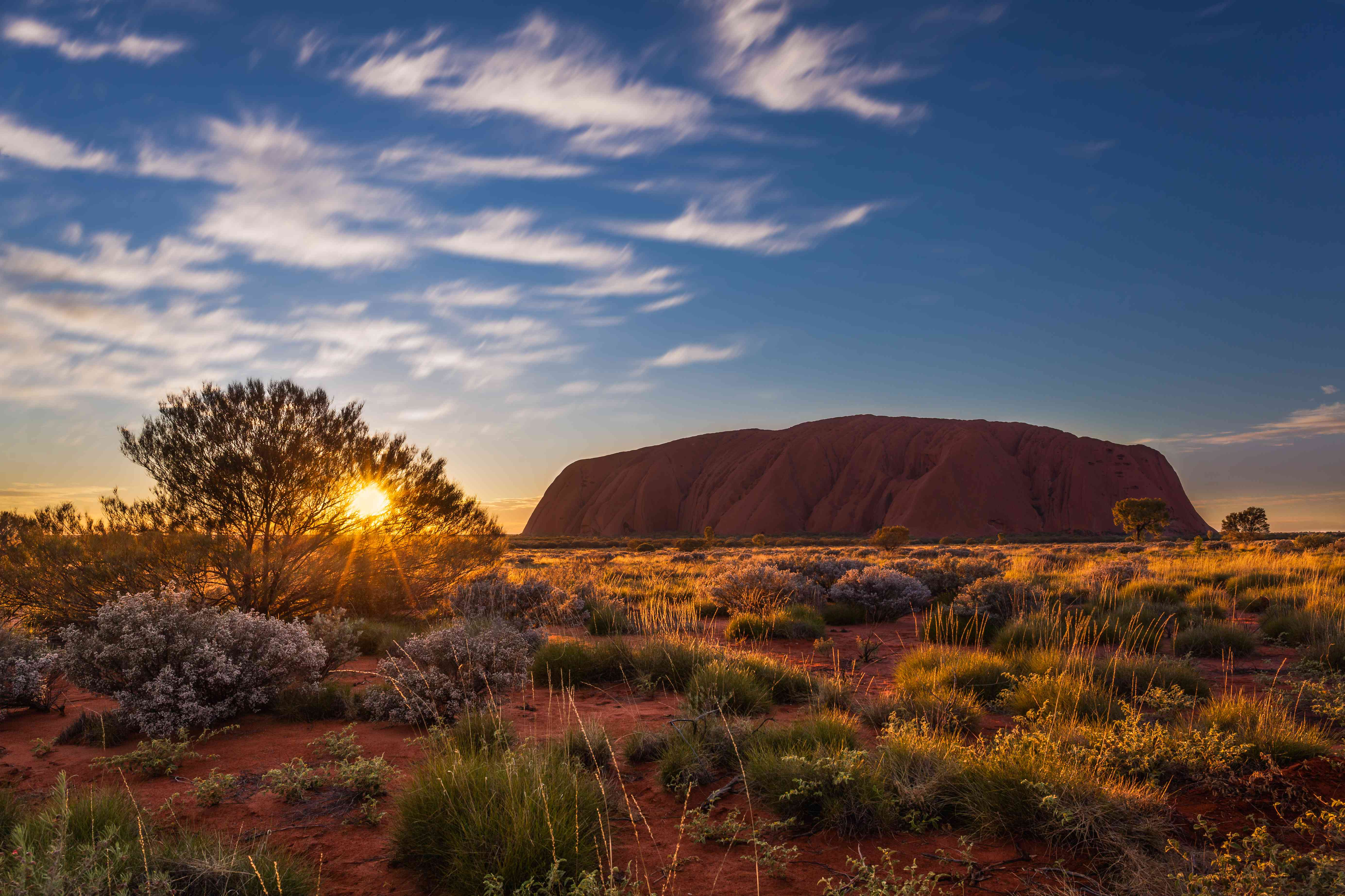 Sun rising over Uluru, also known as Ayers Rock, a large sandstone rock formation in the southern part of the Northern Territory, central Australia.