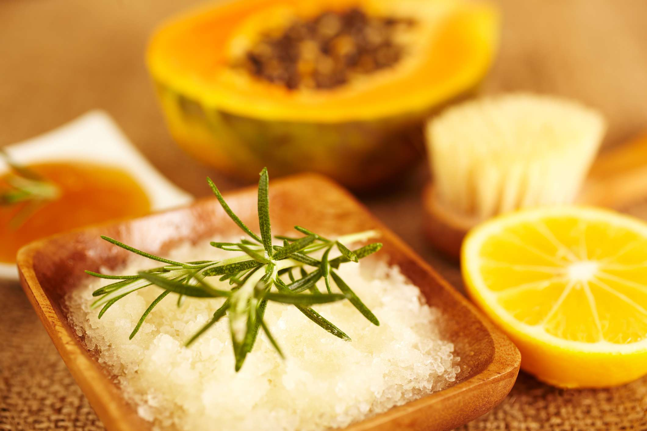 Rosemary sprig on salt scrub surrounded by lemon and melon