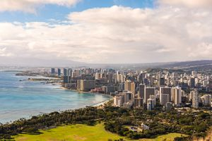 High angle view of skyscrapers in Honolulu along Mamala Bay with lush green trees in the foreground and blue sky with white clouds above on a sunny day