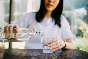 woman pouring water from a glass bottle in to a glass