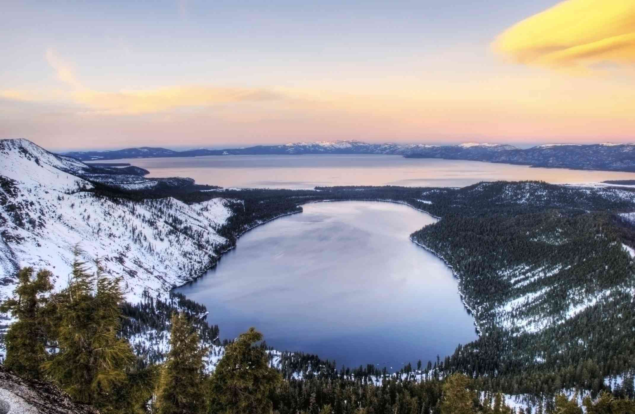 An aerial view of Lake Tahoe with snowy forest around it and a sunset in the distance.
