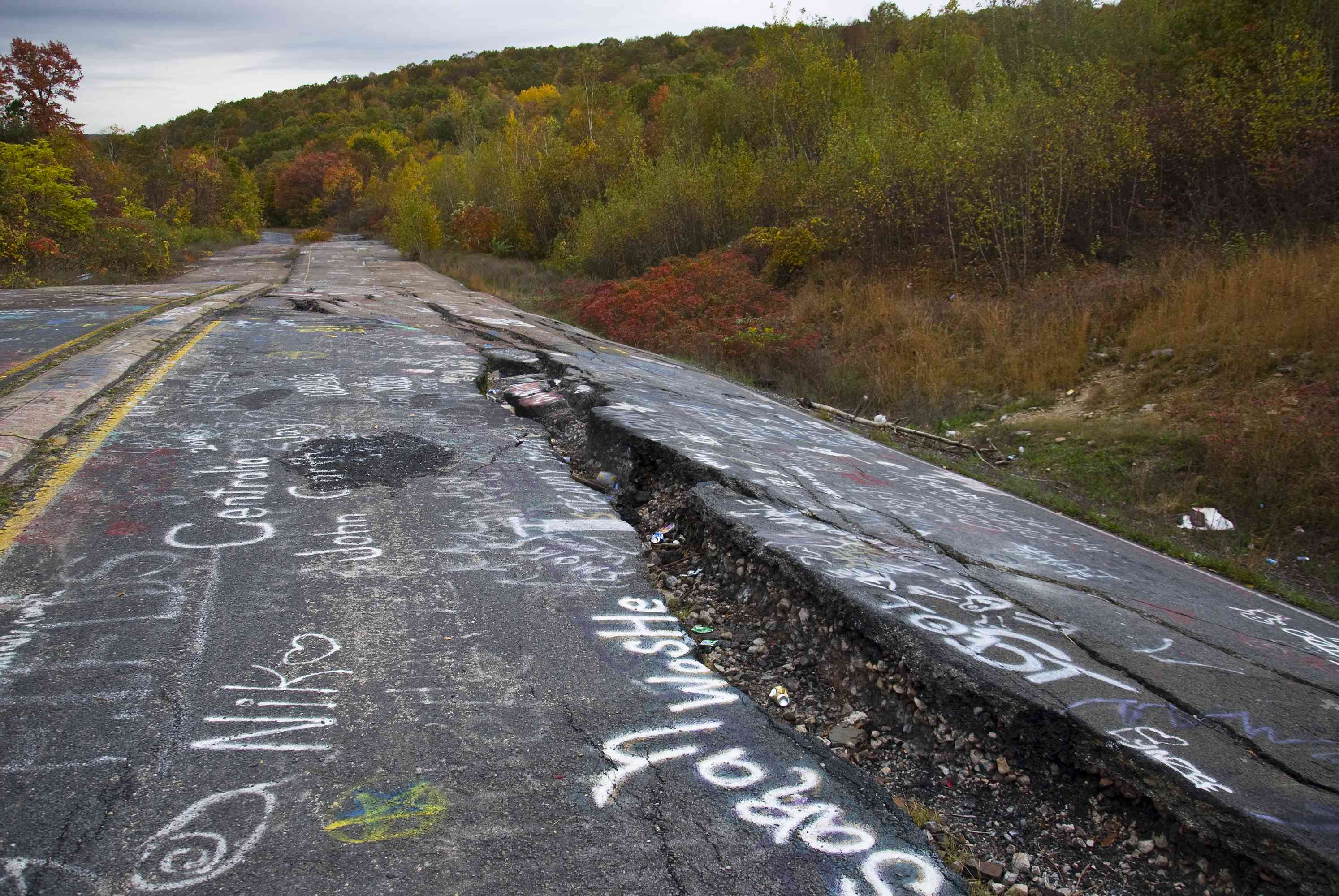 Low-angle view of cracked asphalt due to underground fire
