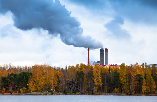 Factory smoke emissions billow out from behind a lake and forest