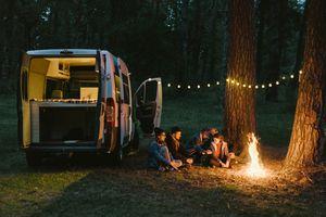 Friends sitting around campfire next to campervan