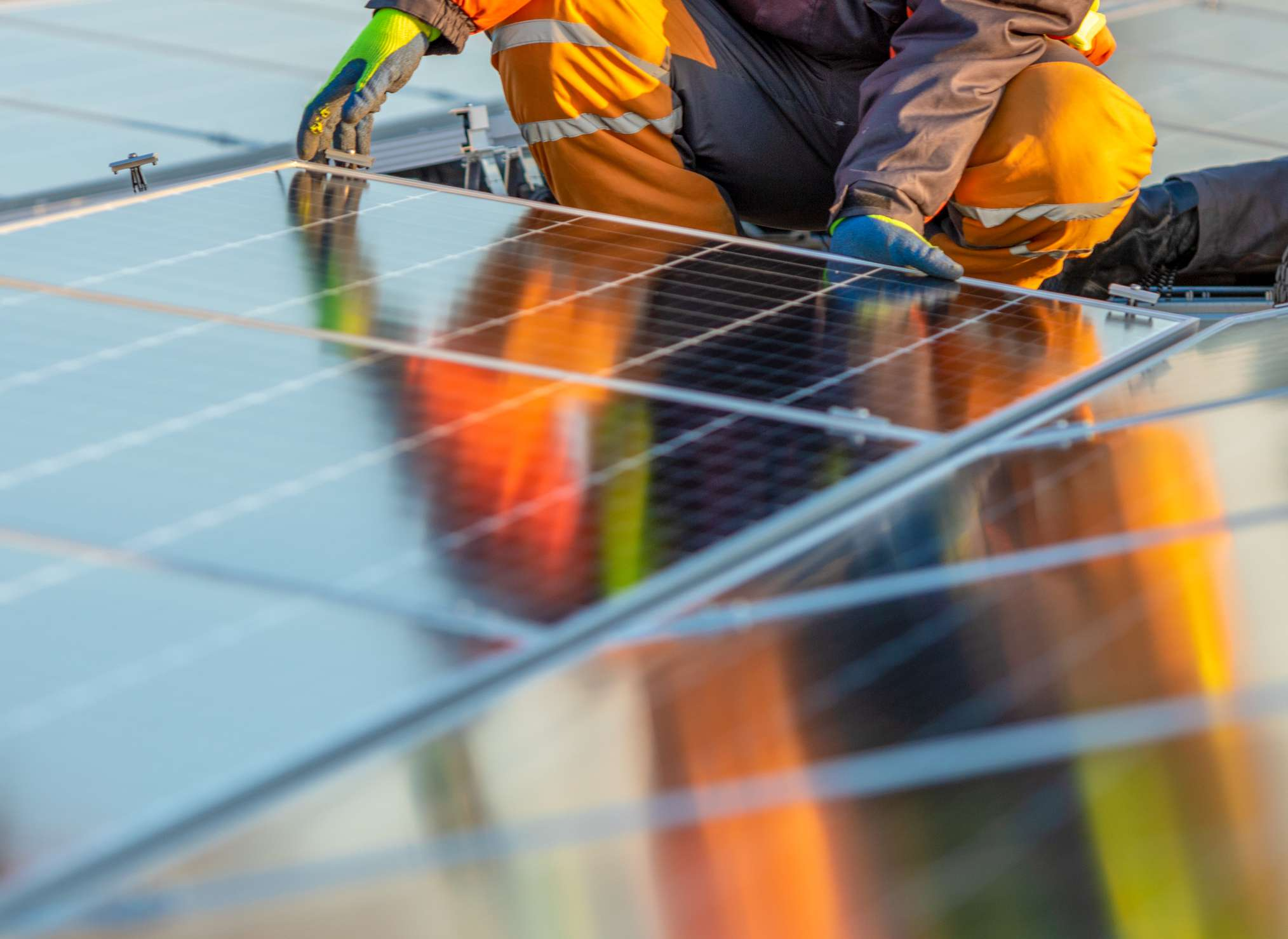 A person installing solar panels on a roof.