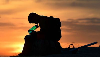 A child looks at his water bottle as the sun sets on June 15, 2021 in Los Angeles, California as temperatures soar in an early-season heatwave.