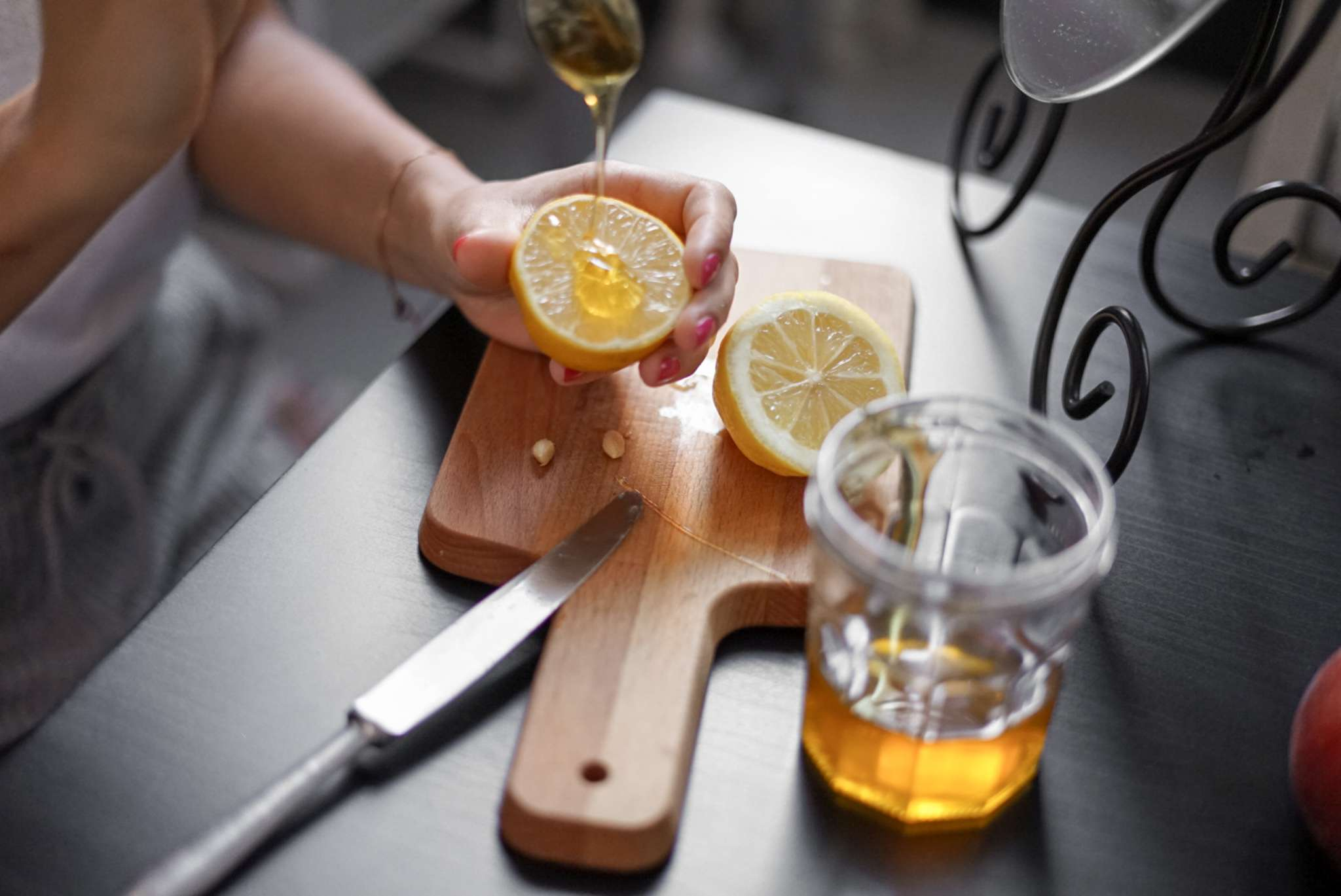 woman drizzles honey over cut lemon on cutting board for natural beauty treatment