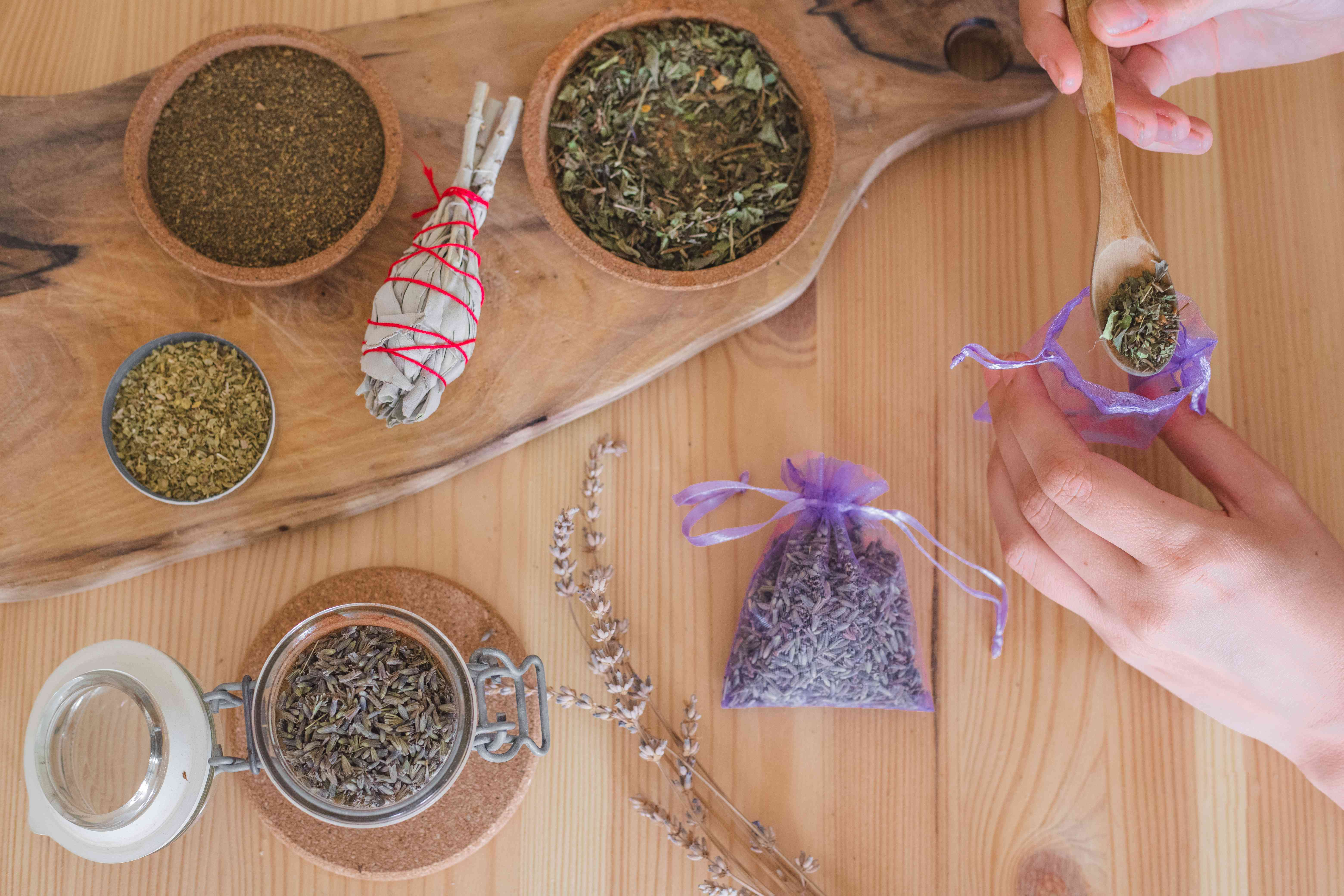 hands make DIY lavender sachets with dried herbs and sage on wooden table