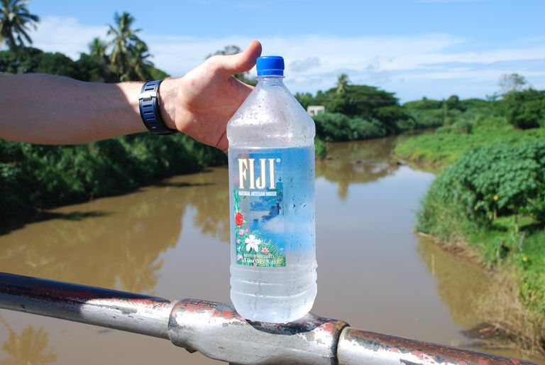 Fiji bottled water being held by a hand balancing on railing over water.