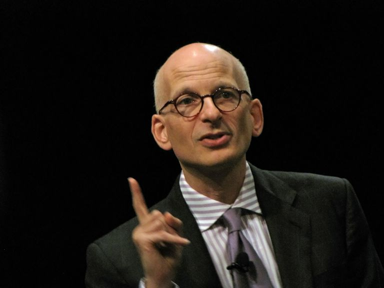 Seth Godin speaking at an event with a black background.