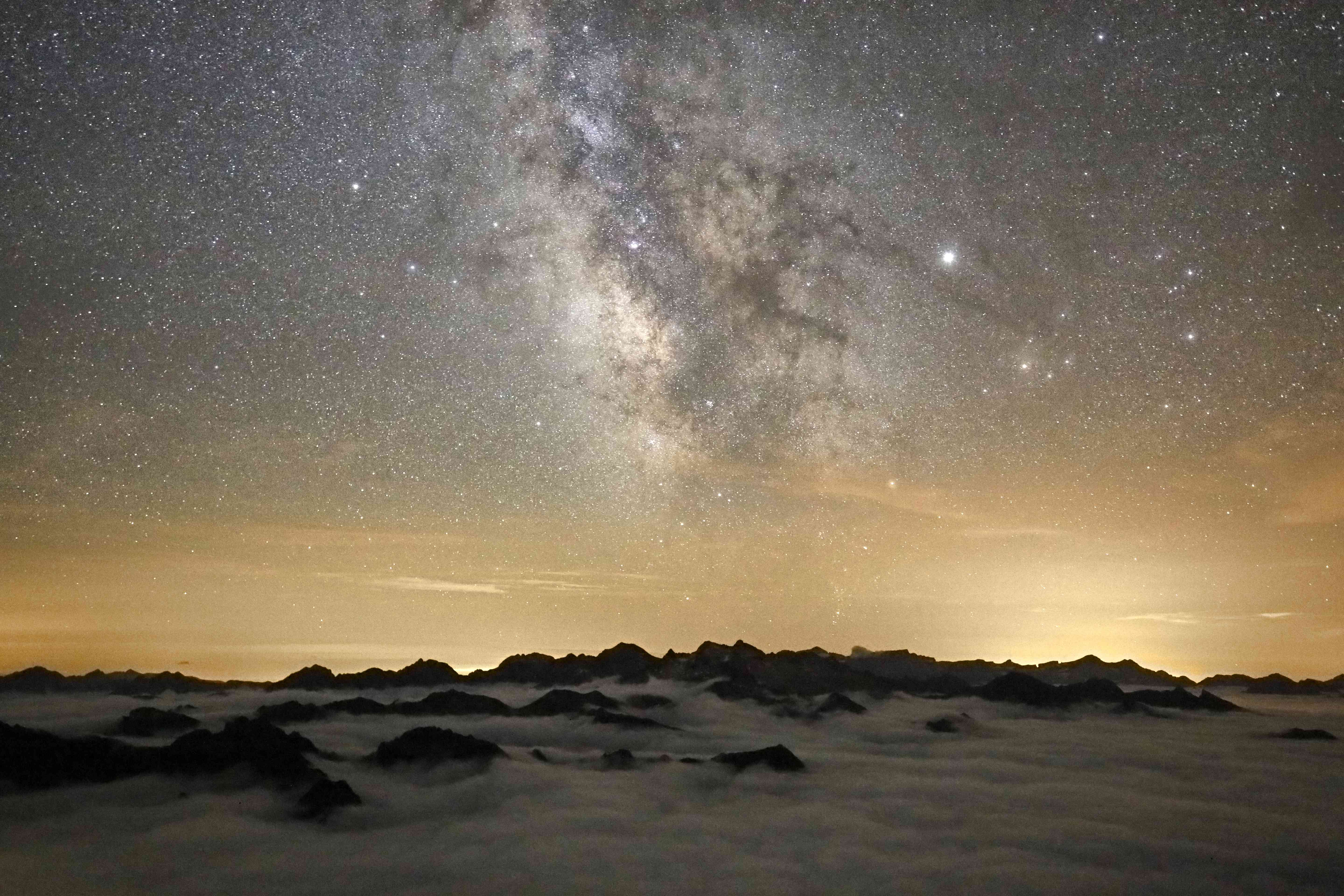 Milky Way over cloudy peaks with light pollution from Barcelona