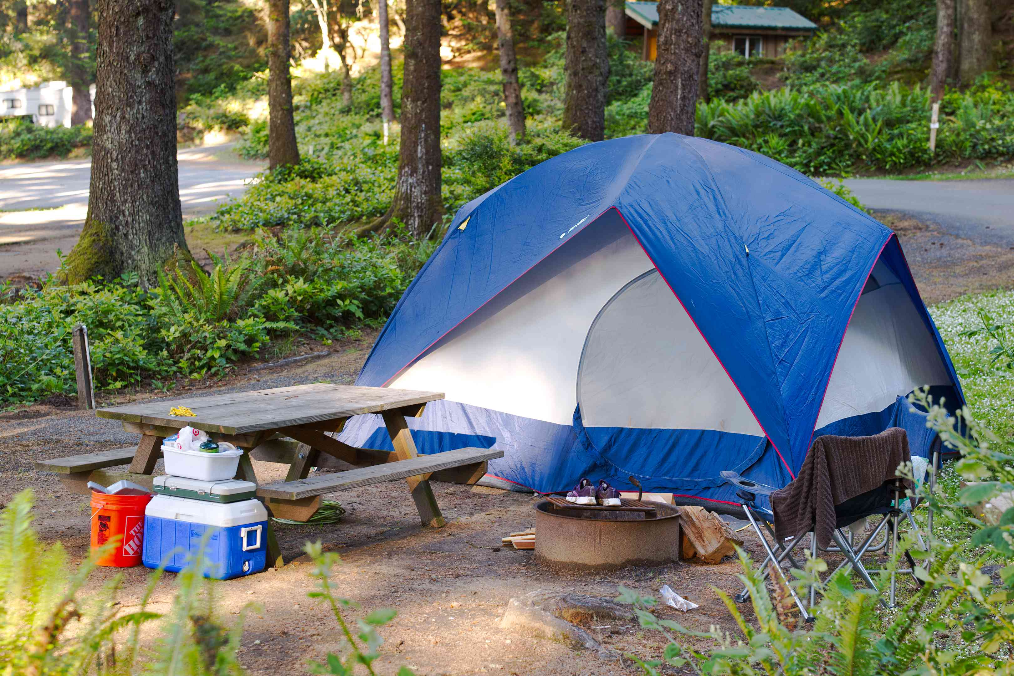 blue and white tent in campsite surrounded by picnic table, coolers, and camping gear