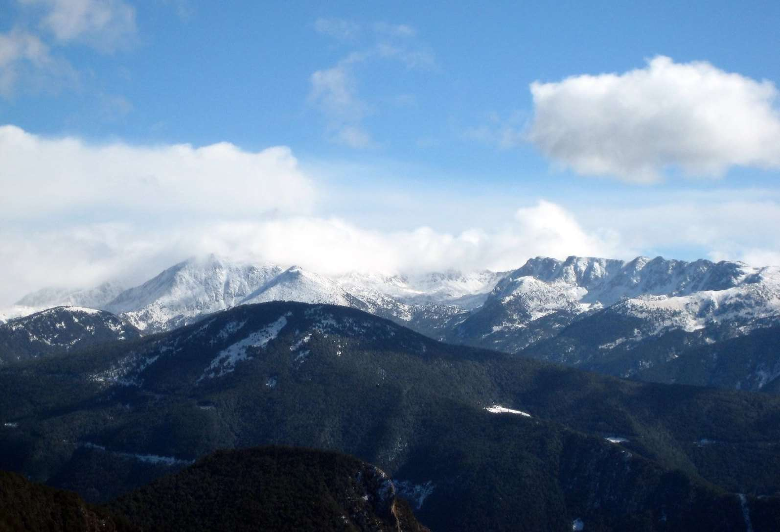 Blue skies with a few clouds hover above snow-capped mountains on the horizon