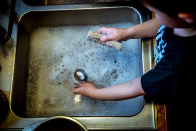 Overhead view of child washing dishes at a sink