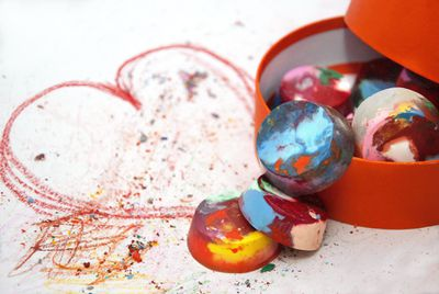 Crayon melts in a box next to a scribbled heart
