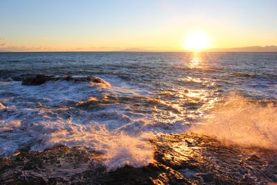rocky ocean coast at sunset with rays spread across waves