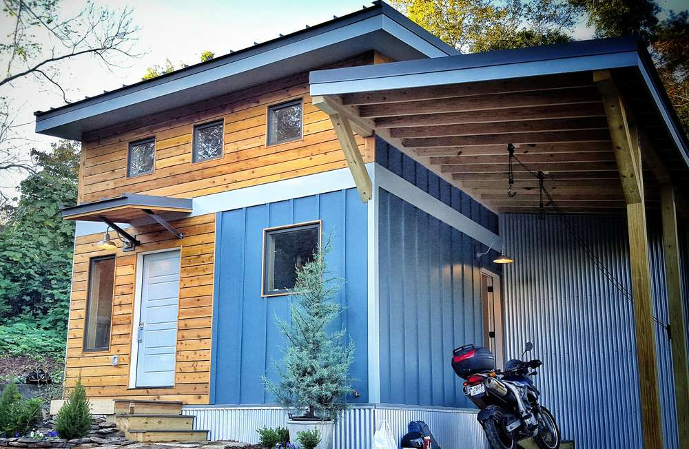 Covered parking area behind tiny home with a motor cycle
