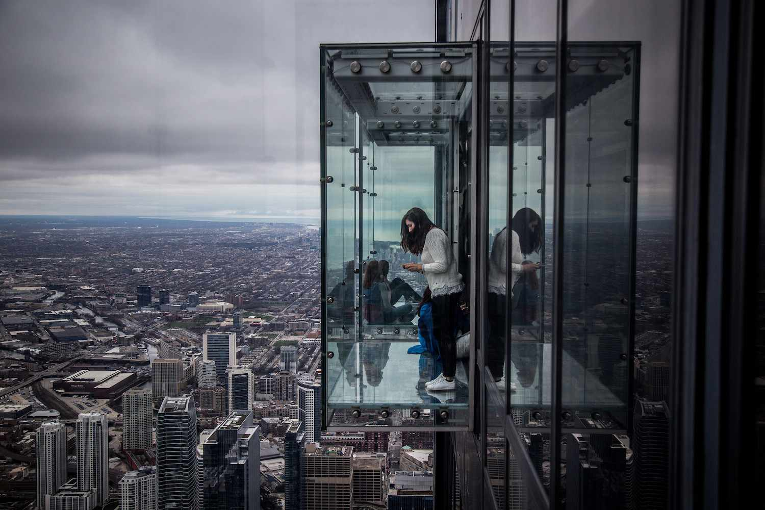 A woman looks down onto the Chicago streets below from The Ledge at Willis Tower