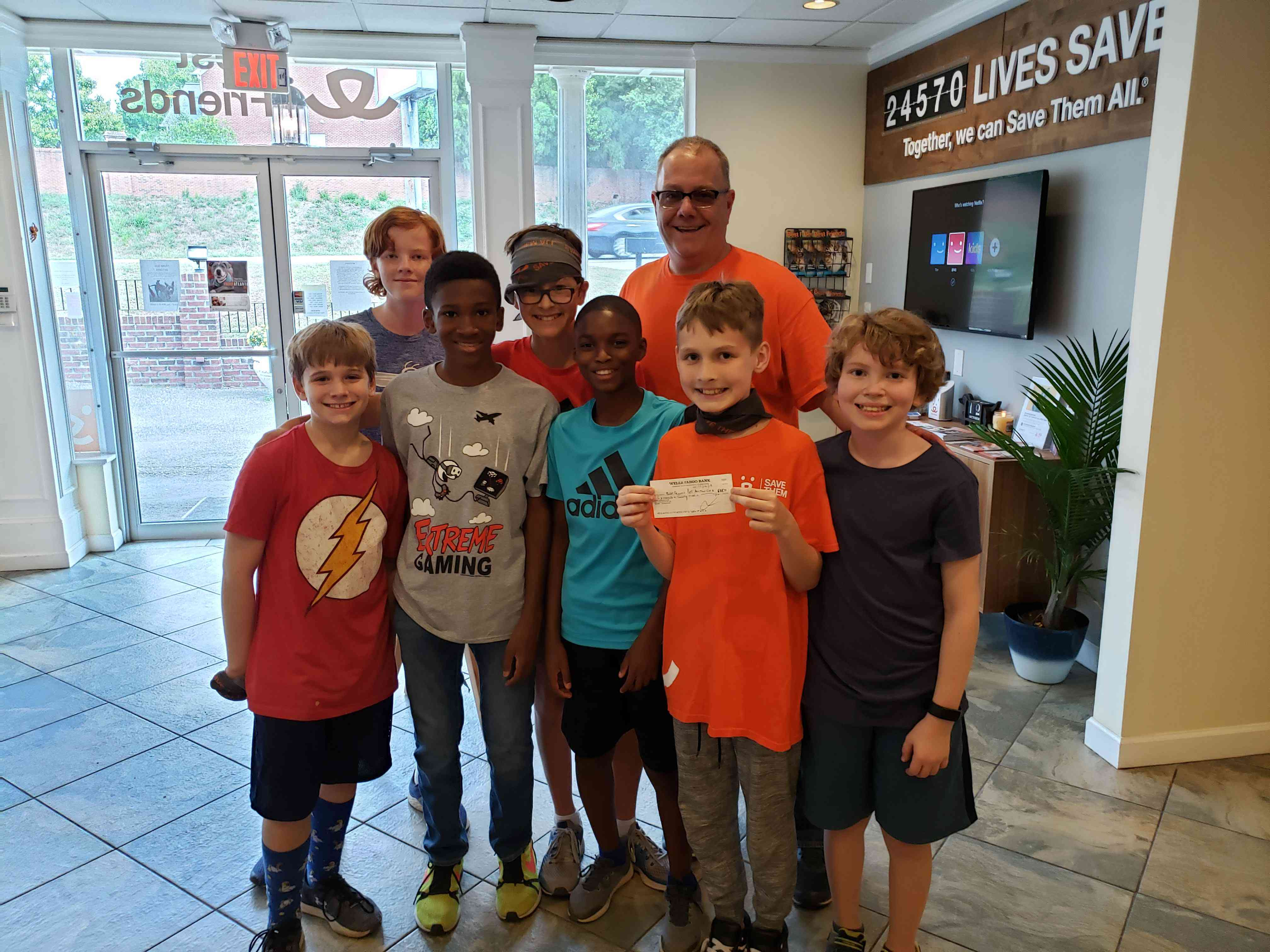 Jack and his friends present a $700 check to Best Friends.