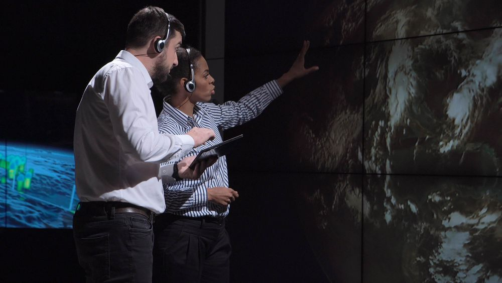 two scientists observing and tracking hurricane on map and analyzing weather. Elements of this image furnished by NASA.
