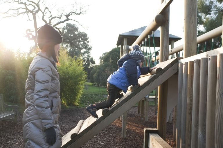 Child climbing a structure at a playground while his mother watches