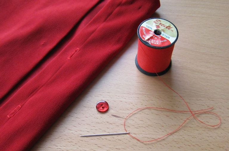 Clothing item, button, needle, and thread on a wooden surface