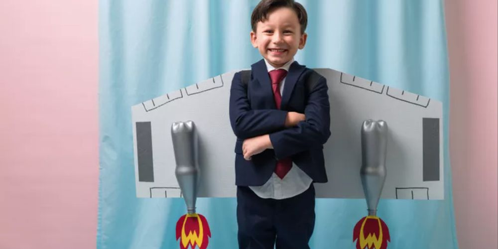 Cute kid in a suit with a cardboard jet pack