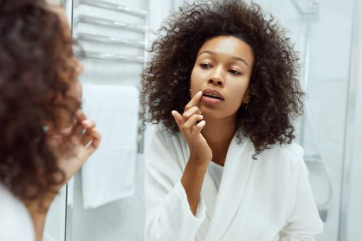 A young black woman applies lip scrub to her lips.