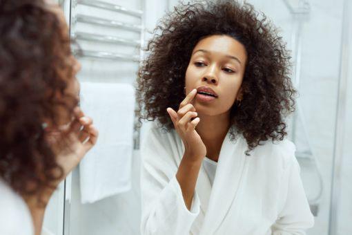 A young black woman applies lip scrub to her lips.