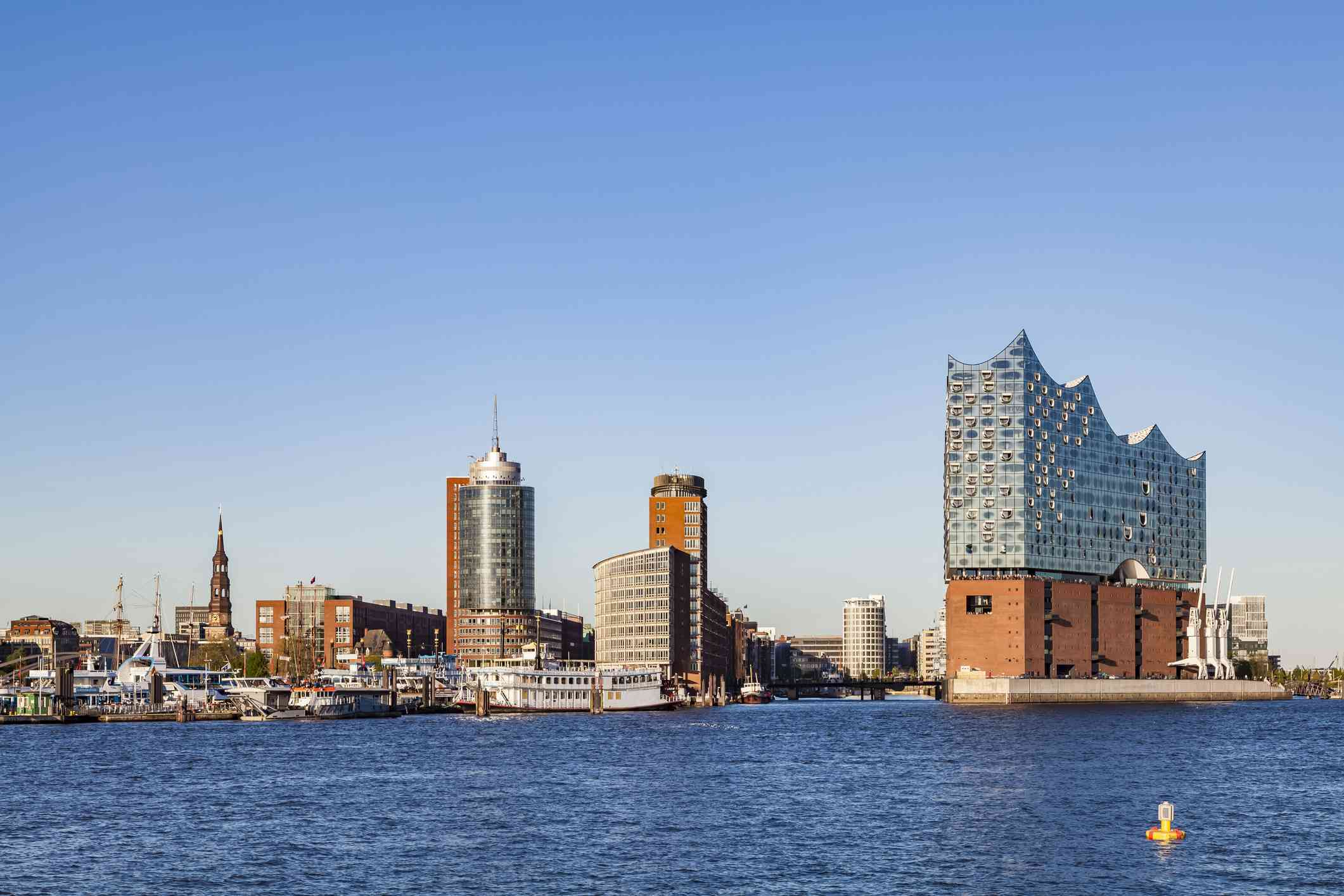 view across the blue water of the harbor of elbphilharmonie Hamburg on the right, a multi-use building completed in 2017, with several brick floors at the lower level and a modern glass tower above, next to new and old buildings in Hamburg's harbor,