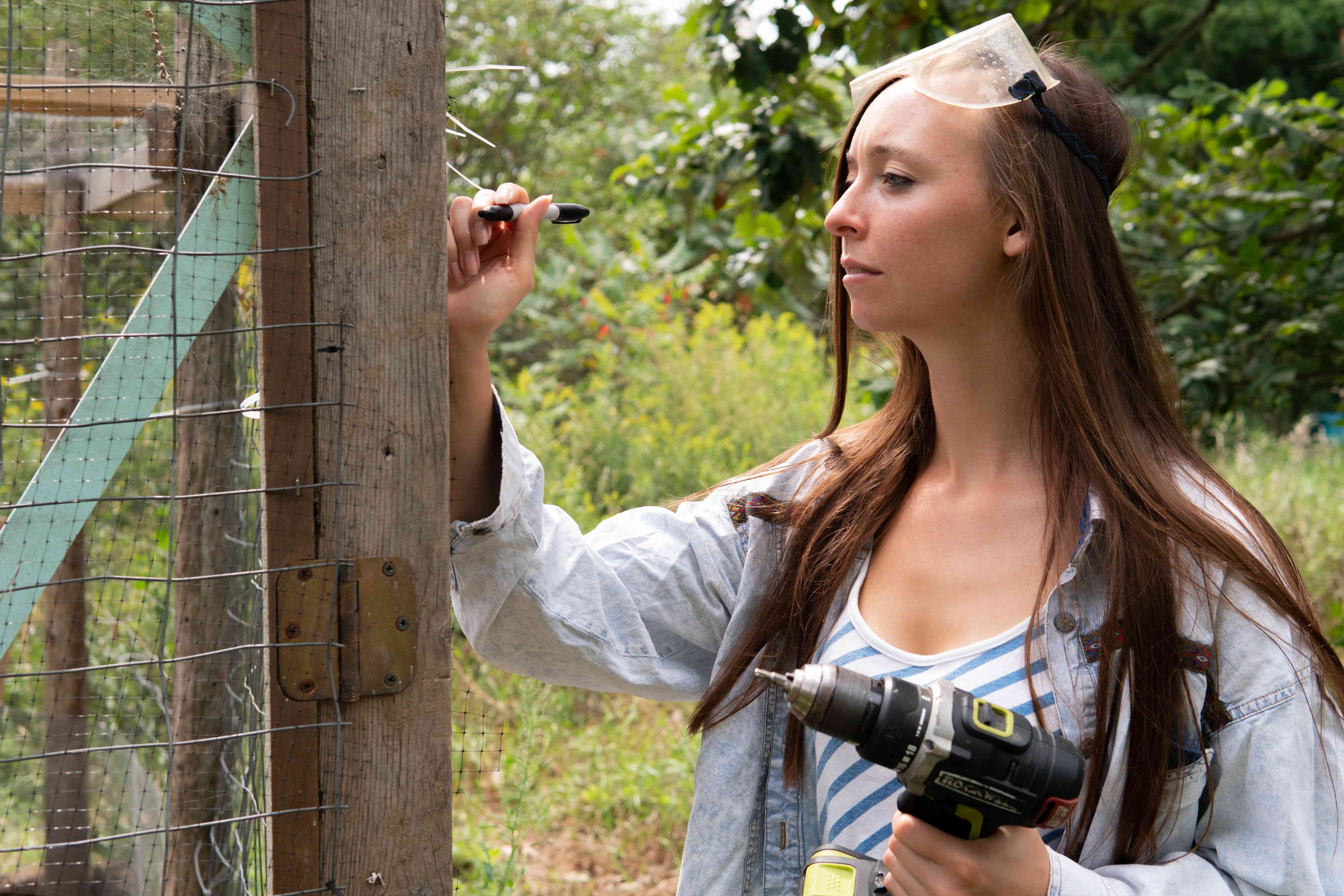 young farmer with drill works on building a chicken coop outside