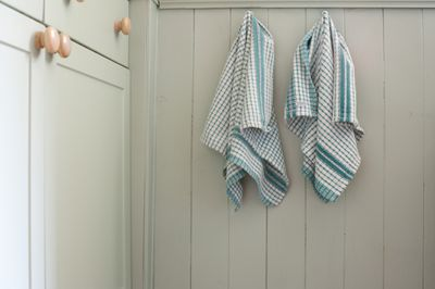 Two dish towels hanging on hooks next to a cabinet