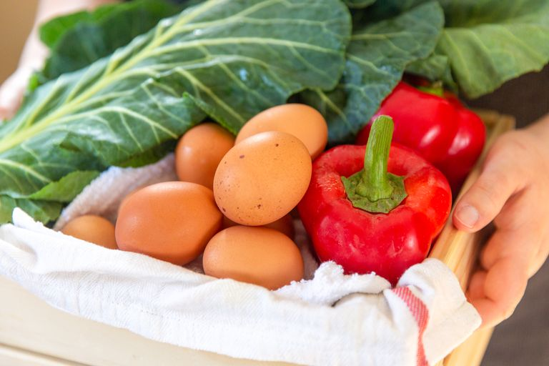 hands hold wooden box with vegetables and eggs