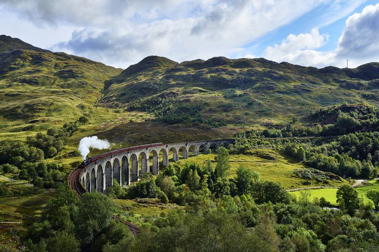 Aerial view of the lush green hills of the Scottish Highlands over the Glenfinnan viaduct with the Jacobite Steam Train passing over it under a blue sky with white clouds