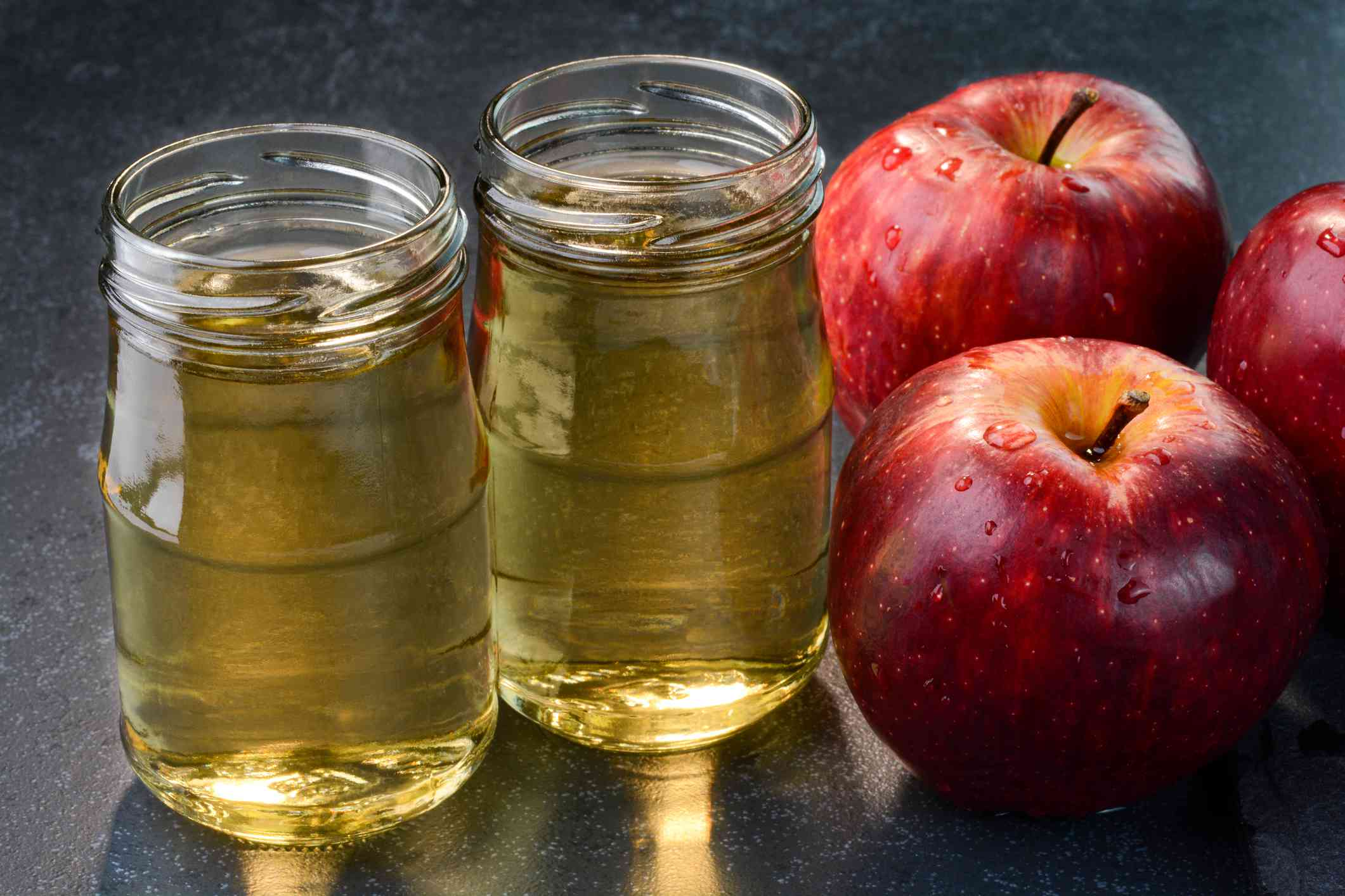 Two small jars of apple cider vinegar sit next two three apples covered in drops of water