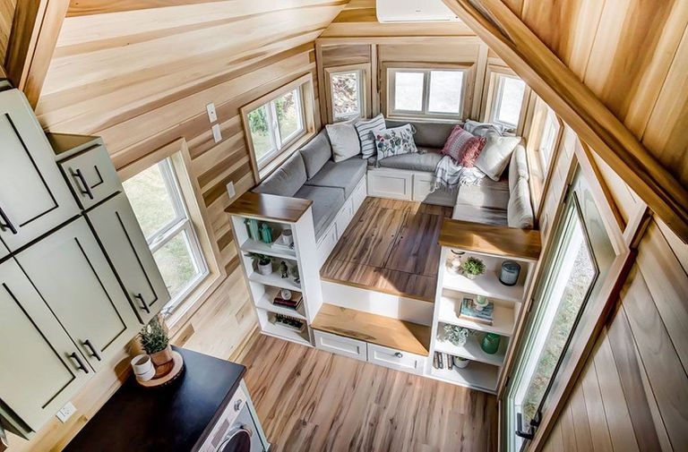 Interior view of a tiny home, with a bench seat sectional in the center