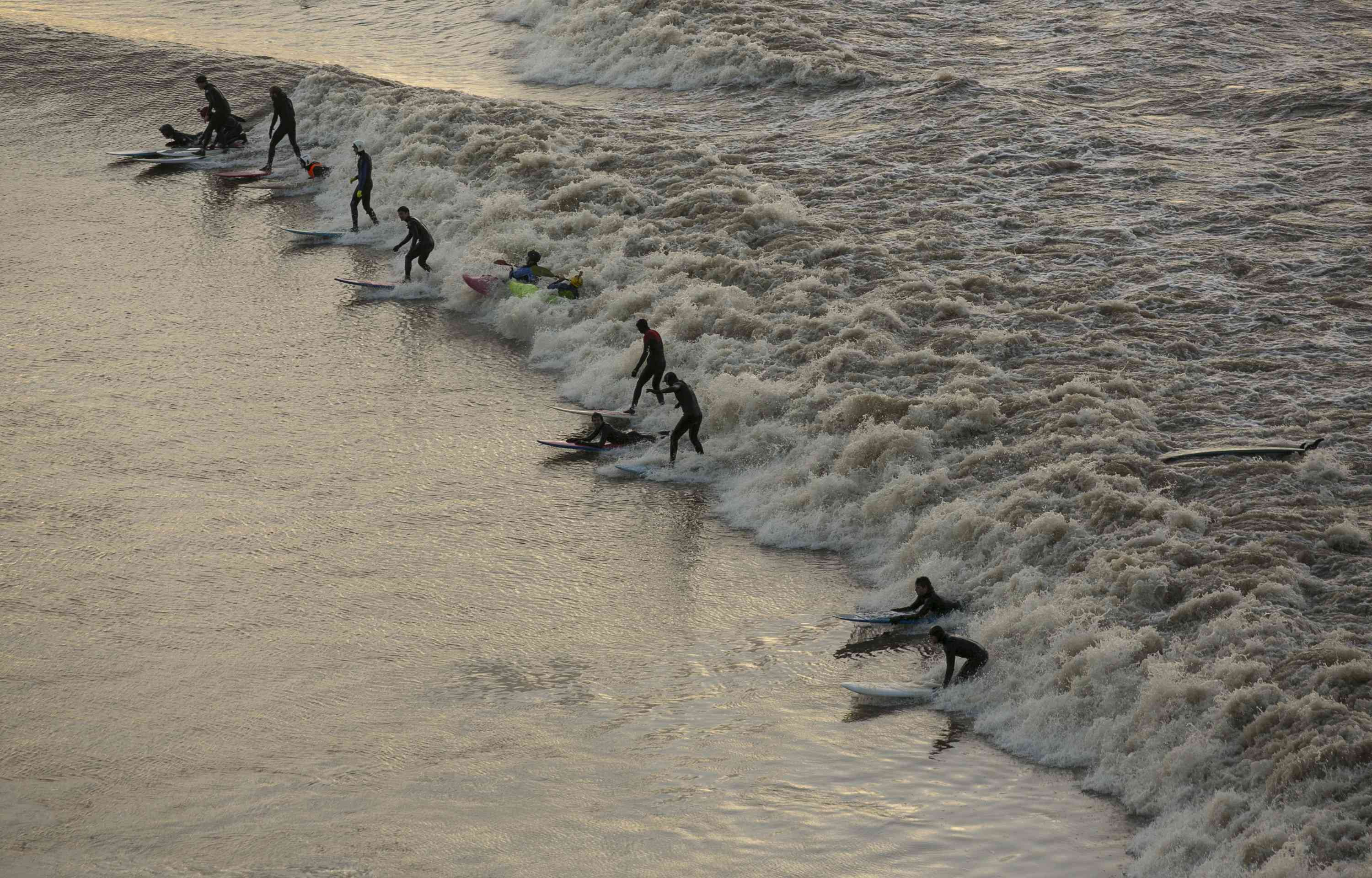 A group of 10 surfers attempt to ride on a rare maximum five star Severn bore viewed from Newnham overlooking the River Severn